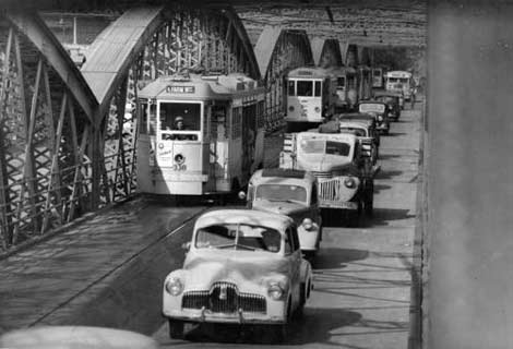 Cars and trams travelling along Victoria Bridge, Brisbane, 1952